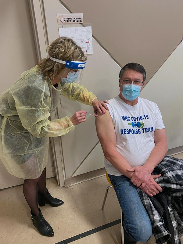 Image of Nurse Paula administering the COVID-19 vaccination to Mike